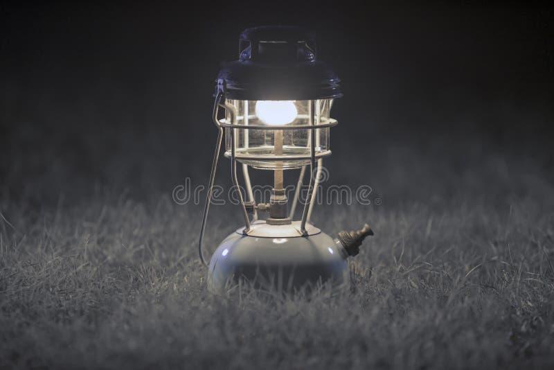 Vecchie lampade di cherosene d'ottone, lampada d'ottone antica, lanterna di campeggio di notte, sul fondo grigio dell'erba Fuoco  immagini stock libere da diritti