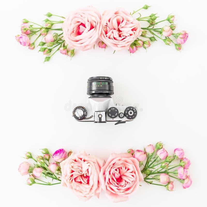 Vecchie macchina fotografica e rose, germogli e foglie su fondo bianco Disposizione piana, vista superiore Retro priorità bassa fotografie stock