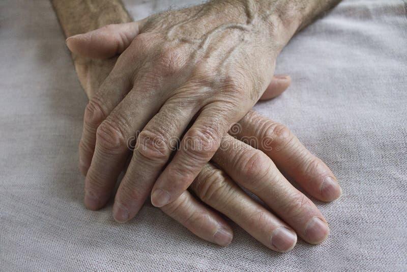 Vecchie mani spiegazzate immagine stock