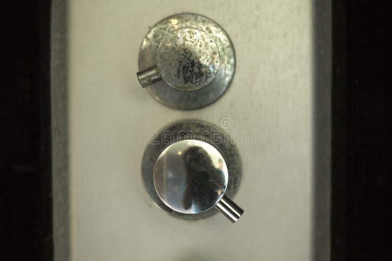 Vecchie manopole ossidate per caldo e acqua fredda nella doccia fotografia stock libera da diritti