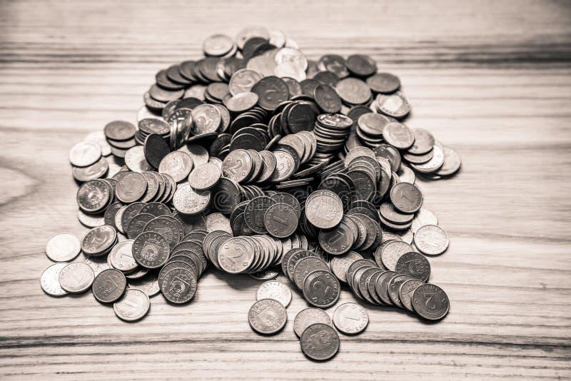 Vecchie monete lettoni su un fondo di legno - lo d'annata monocromatico immagini stock