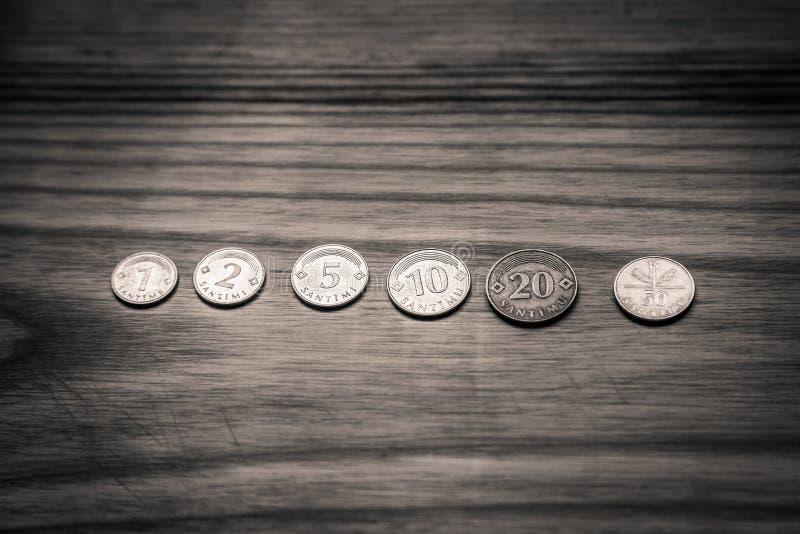 Vecchie monete lettoni su un fondo di legno - lo d'annata monocromatico fotografie stock