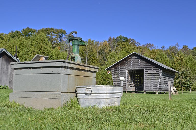 Vecchie pompa idraulica, vasca da bagno e greppia del cereale immagine stock