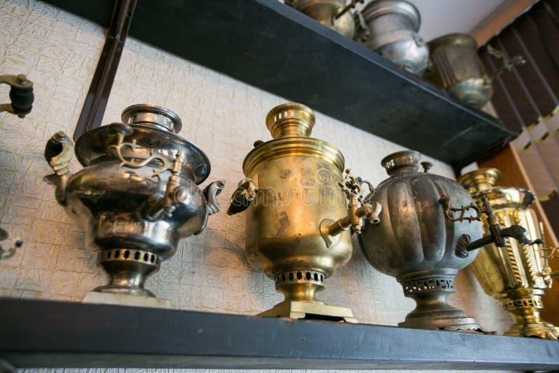 Vecchie samovar bronzee sullo scaffale in un negozio di ciarpame fotografie stock
