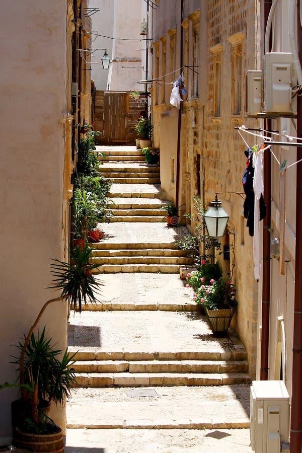 Vecchie scale sulle costruzioni strette della pietra di via immagine stock libera da diritti