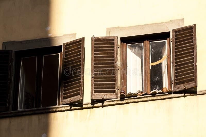 Vecchie scarpe che stanno sulla finestra di legno tradizionale moda a Firenze, Italia fotografie stock