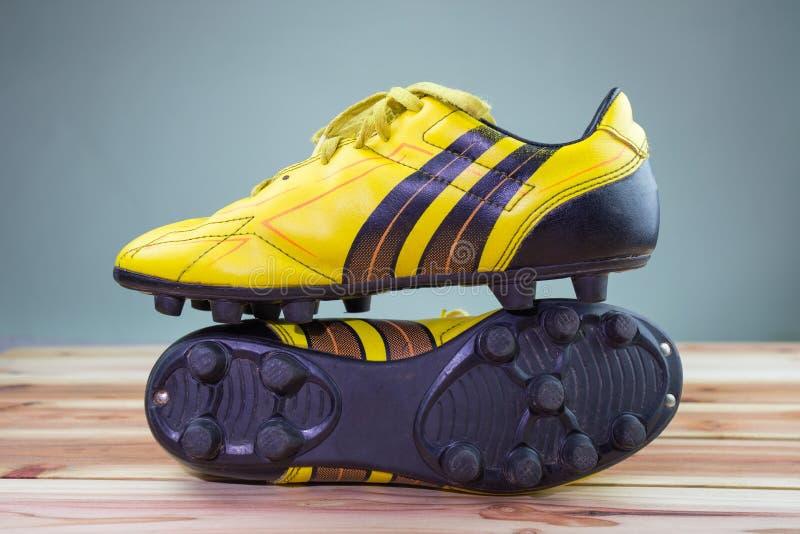 Vecchie scarpe gialle disposte su un bordo di legno, luce morbida grigia di calcio del fondo immagine stock