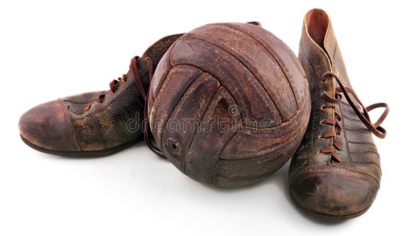 Vecchie scarpe per calcio e pallone da calcio fotografia stock libera da diritti