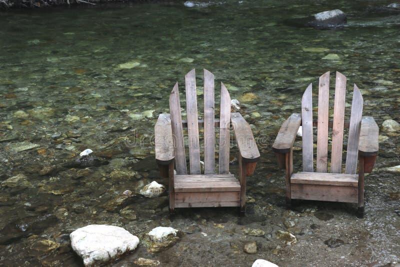 Vecchie sedie di legno in un letto di fiume, Big Sur, CA del adirondack immagini stock