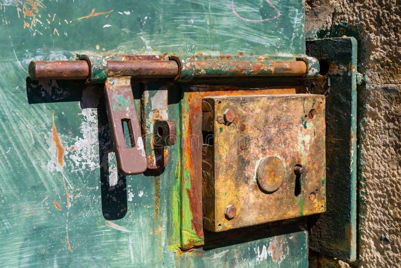 Vecchie serratura e cerniera di porta del ferro su una porta del metallo fotografie stock