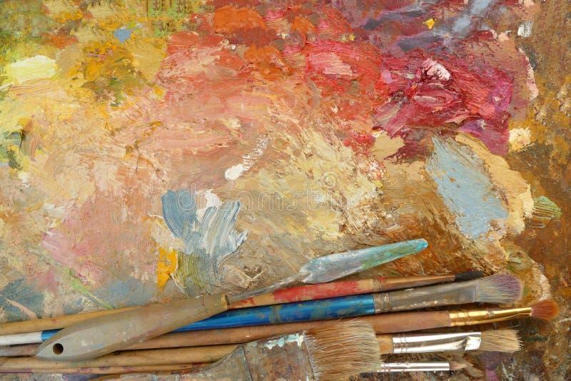 Vecchie spazzole di arte su una tavolozza con le pitture Vista superiore fotografie stock libere da diritti