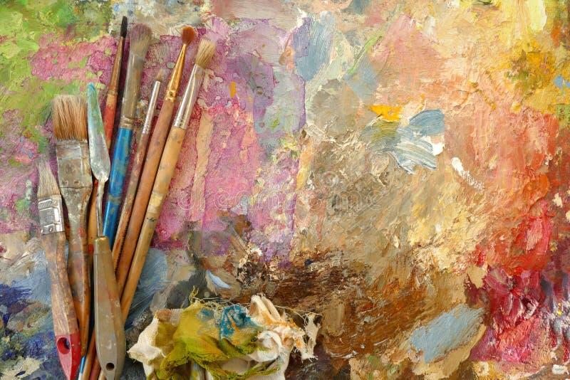 Vecchie spazzole di arte su una tavolozza con le pitture Vista superiore immagini stock
