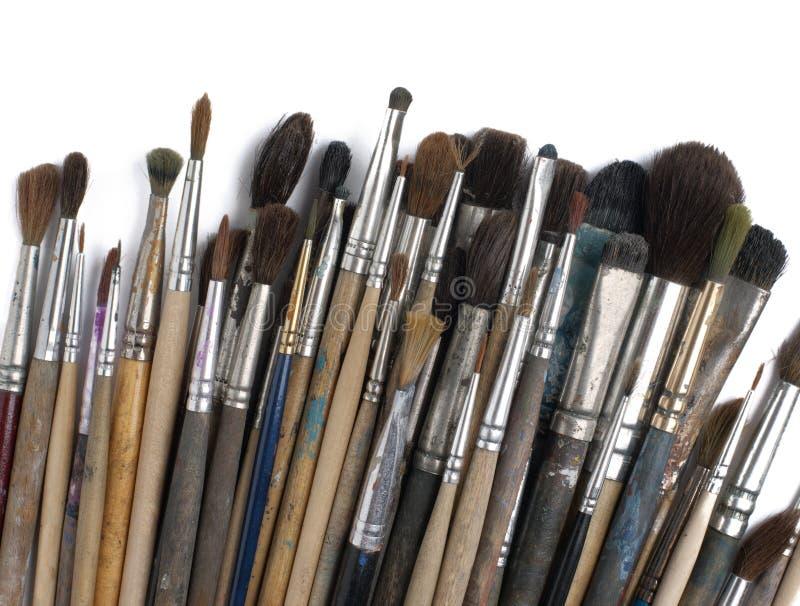Vecchie spazzole di pittura sporche assortite. Isolato sopra immagine stock