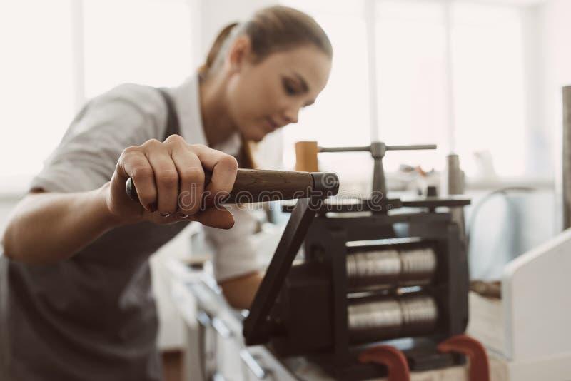 Vecchie tecnologie Giovane orafo femminile che elabora metallo sul laminatoio in officina fotografia stock