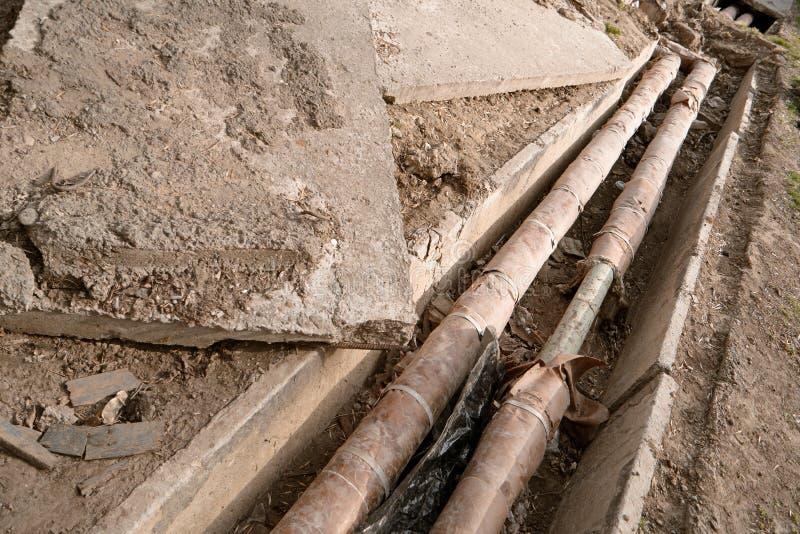 Vecchie tubature dell'acqua arrugginite in fossa concreta L'utilità sotterranea ed il tubo d'alimentazione pongono al cantiere ri fotografia stock libera da diritti