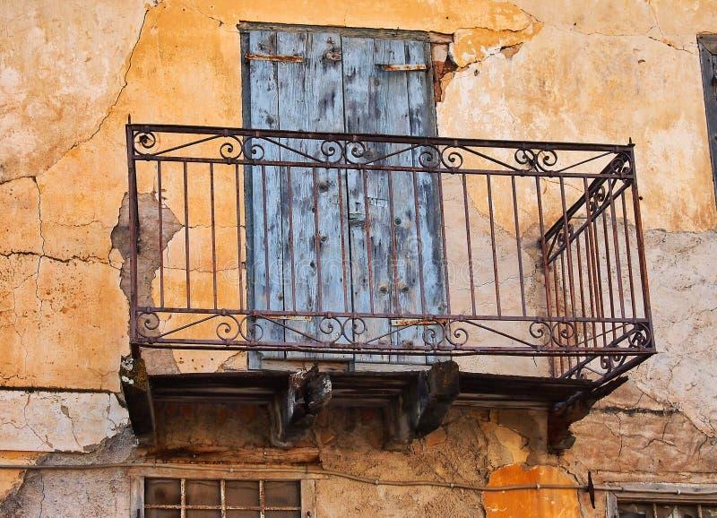 Vecchio balcone del pizzo del ferro sulla Camera sbiadita dello stucco, Grecia fotografia stock libera da diritti