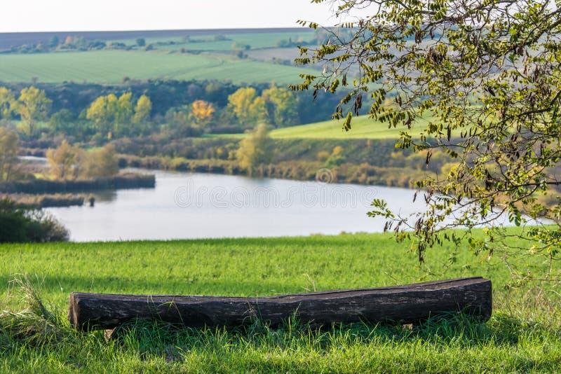 Vecchio banco davanti ad un bello paesaggio collinoso con il lago immagini stock