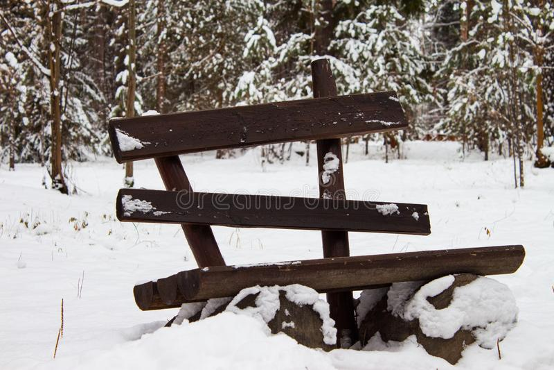 Vecchio banco di legno vuoto in parco innevato Priorità bassa di inverno all'aperto immagine stock