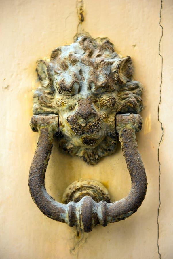 Vecchio battitore di porta arrugginito della testa del leone del ferro su una porta bianca immagini stock