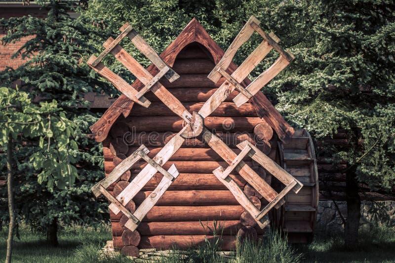 Vecchio bello mulino a vento di legno nella campagna con gli alberi verdi immagine stock libera da diritti