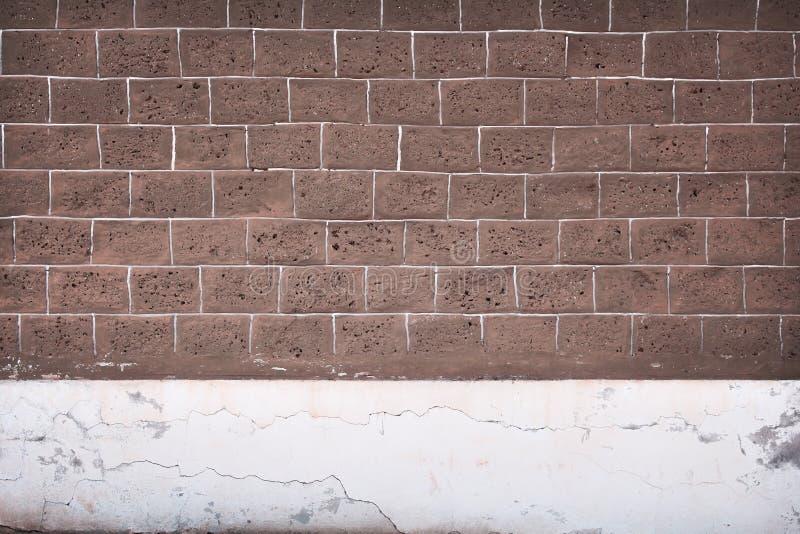 Vecchio blocco in calcestruzzo con la pittura bianca scura e di marrone su struttura del fondo della parete fotografia stock