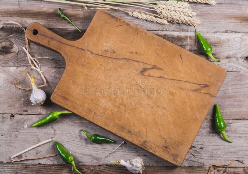 Vecchio bordo della cucina con l'aglio ed il grano del peperone verde fotografia stock