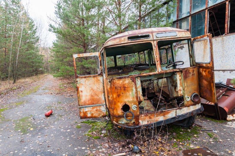 Vecchio bus arrugginito distrutto alla fabbrica nella città del fantasma di Pripyat, nella zona della centrale atomica di Cernoby fotografie stock libere da diritti