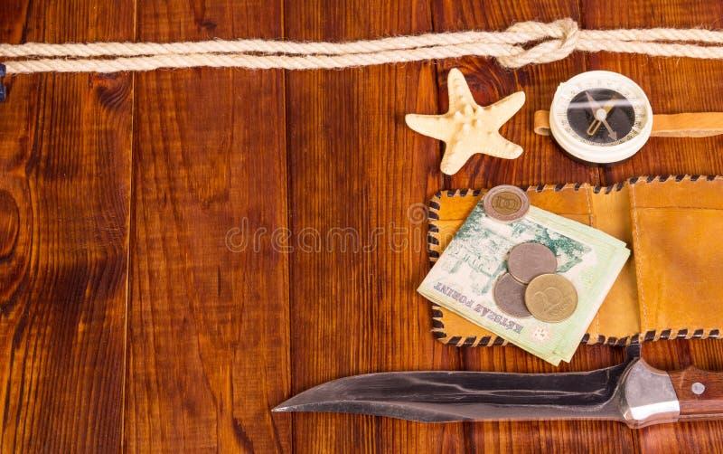 Vecchio, bussola, soldi, coltello e stelle marine sul legno di buio del fondo immagini stock libere da diritti