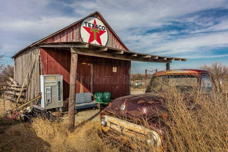Vecchio camioncino abbandonato davanti alla stazione abbandonata di Texaco, zona a distanza del Nebraska fotografie stock libere da diritti