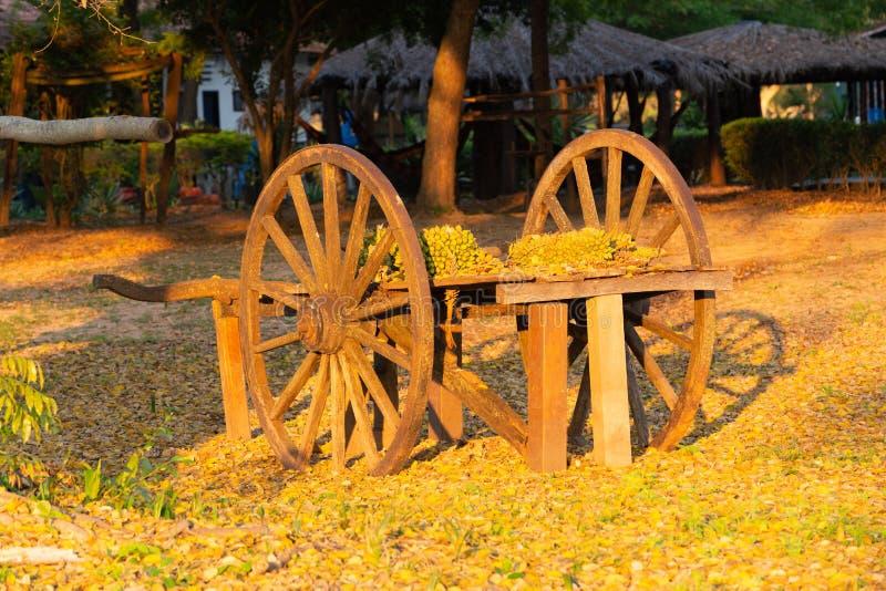 Vecchio carretto pittoresco con le grandi ruote lasciate per la decorazione alla luce del tramonto fotografia stock