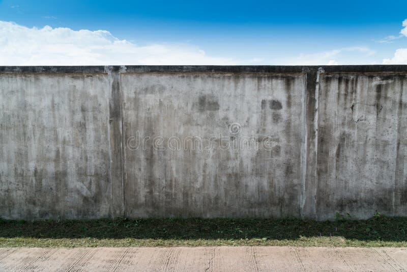 Vecchio cemento o muro di cemento grigio incrinato con cielo blu come fondo Fondo strutturato dello stucco intonacato lerciume fotografia stock