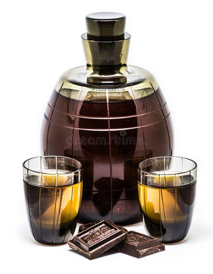 Vecchio cognac in bottiglia di vetro e due vetri di colpo fotografia stock libera da diritti