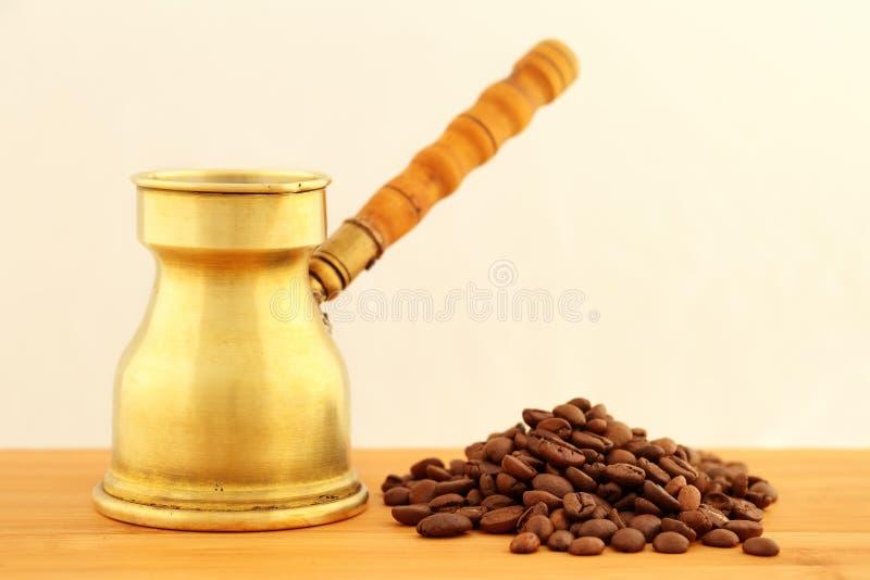 Vecchio, dzhezve turco d'ottone d'annata della caffettiera con la maniglia di legno scolpita e un mucchio dei chicchi di caffè ar fotografie stock