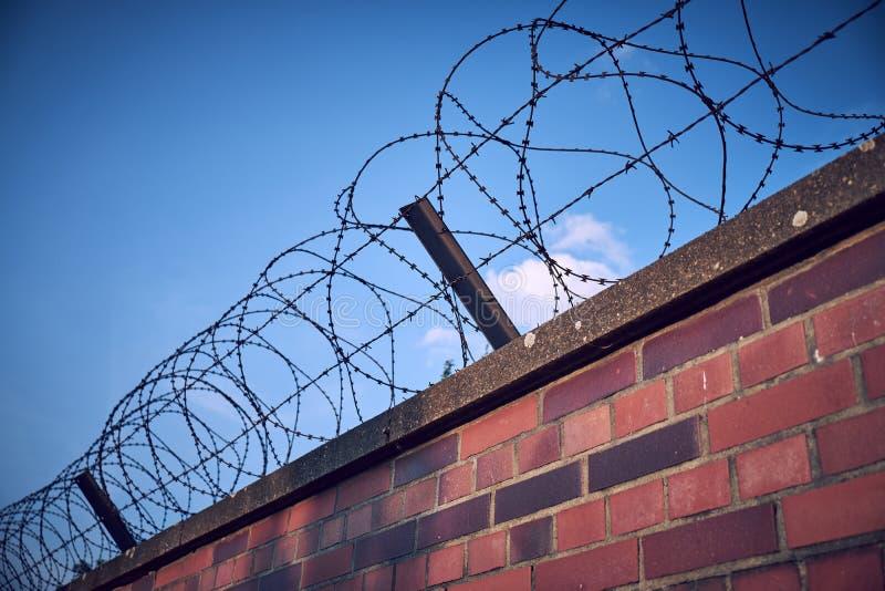 Vecchio e filo spinato arrugginito sopra una parete bricked che corre diagonalmente dall'angolo all'angolo del telaio fotografie stock