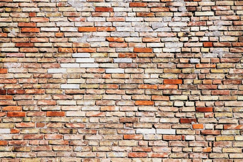 Vecchio e muro di mattoni giallo e rosso grungy stagionato con la crepa visibile come fondo approssimativo rustico di struttura immagine stock libera da diritti