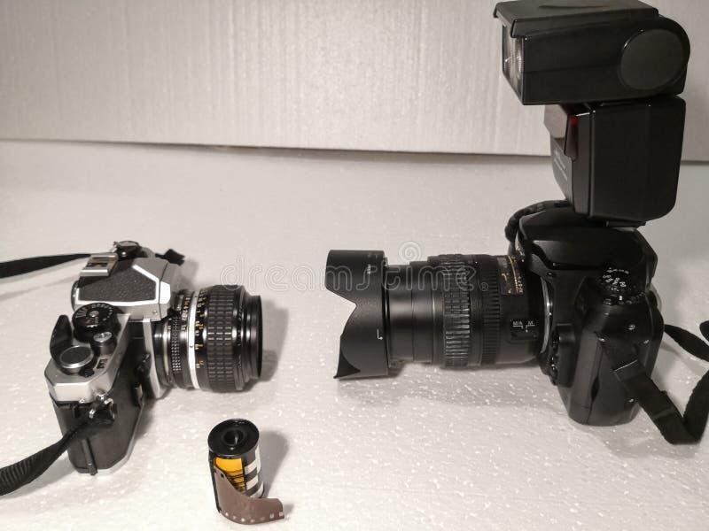 Vecchio e nuova tecnologia per la macchina fotografica macchina da presa 1980 del manuale contro una lente e un lampeggiatore ele fotografia stock