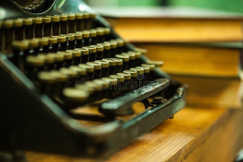 Vecchio e tipo d'annata macchina dello scrittore e mucchi dei libri sulla tavola di legno - fuoco molto selettivo immagini stock
