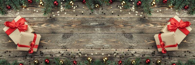 Vecchio fondo di legno di natale Rami dell'abete con le bagattelle e le stelle d'oro Di natale carta orizzontalmente, regali Vist fotografia stock
