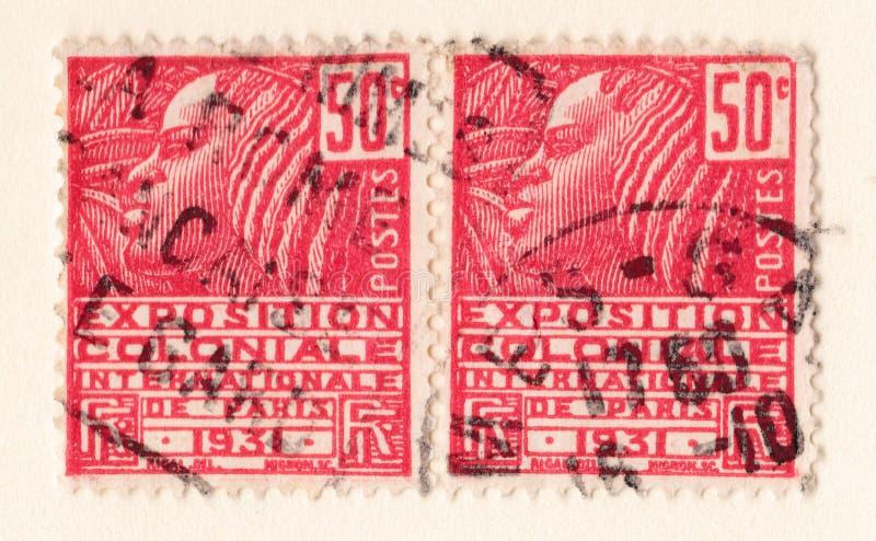 Vecchio francobollo francese rosso con un'illustrazione di una donna africana stilizzata che commemora una mostra coloniale nel 1 fotografie stock