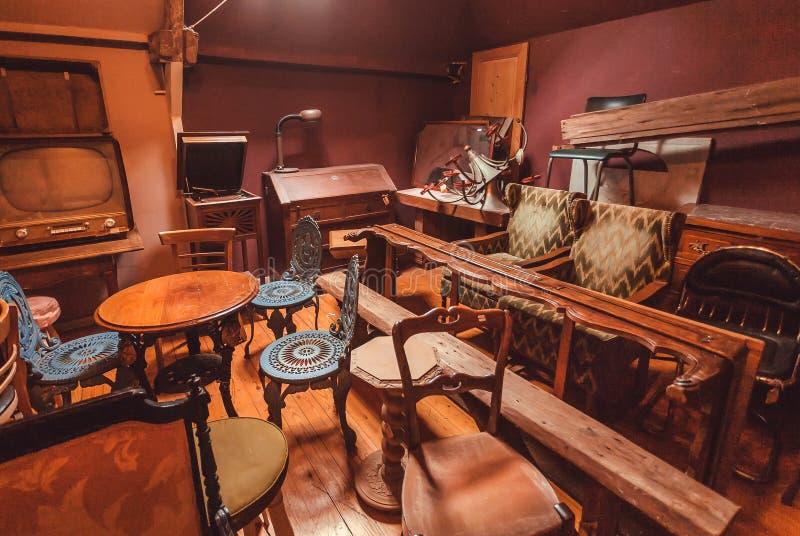 Vecchio gabinetto in negozio di antiquariato con i molti utensile d'annata, decorazione, mobilia di legno, retro poltrone fotografia stock libera da diritti