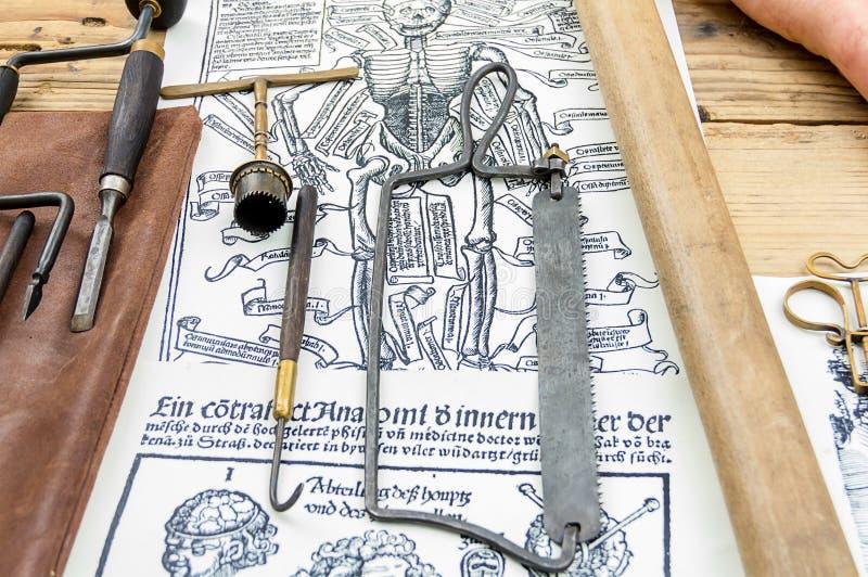 Vecchio gancio chirurgico della sega degli strumenti medici su fondo fotografia stock
