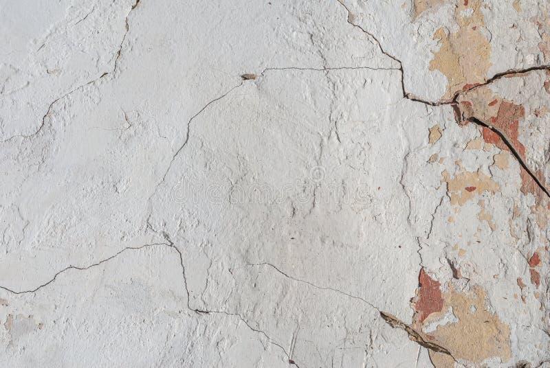 Vecchio gesso scheggiato sul muro di cemento, crepe in vecchio muro di cemento, struttura del fondo immagini stock libere da diritti