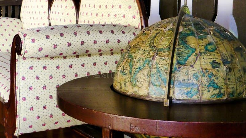 Vecchio globo e sofà antico immagini stock