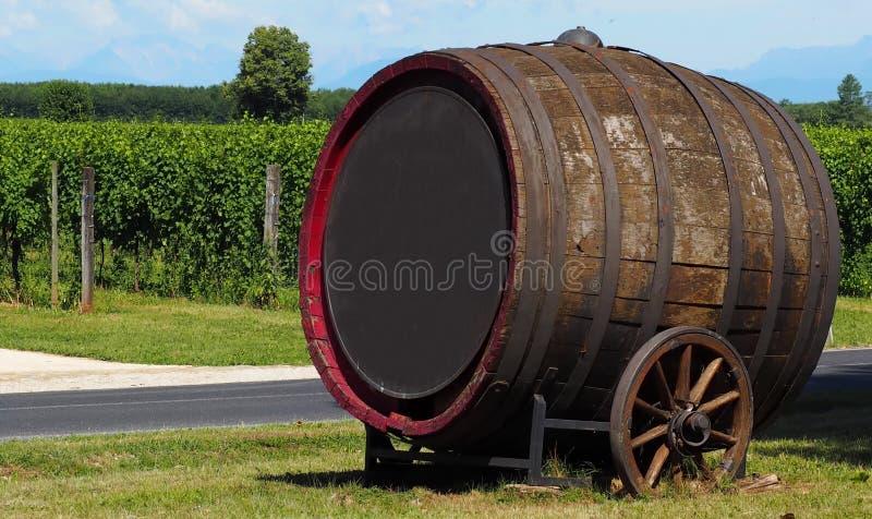 Vecchio grande barilotto di vino inclinato al lato con le ruote di legno davanti ad una vigna È usato come la decorazione e carte immagini stock