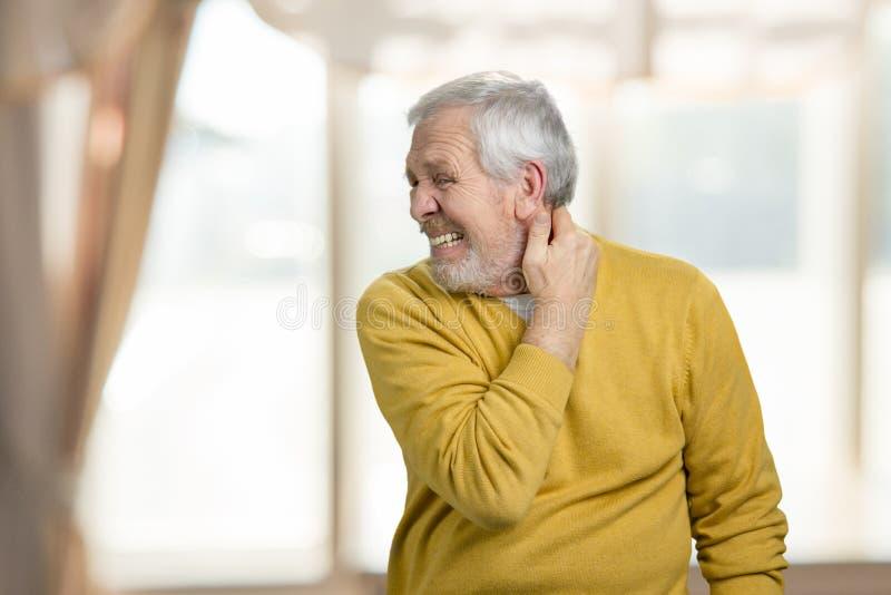 Vecchio granfather che soffre dal dolore al collo fotografia stock