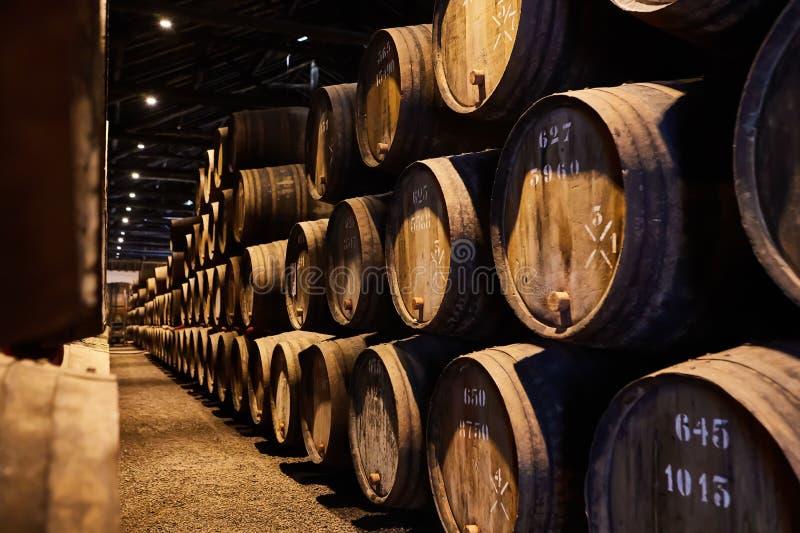 Vecchio ha invecchiato i barilotti di legno tradizionali con vino in una volta allineata in cantina fresca e scura in Italia, Opo fotografie stock