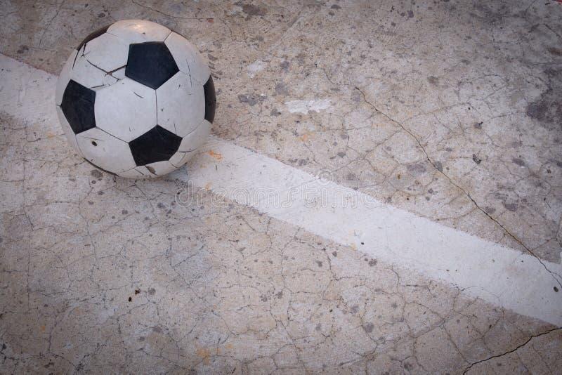 Vecchio ha rovinato il pallone da calcio nocivo messo sul giacimento incrinato del cemento fotografia stock