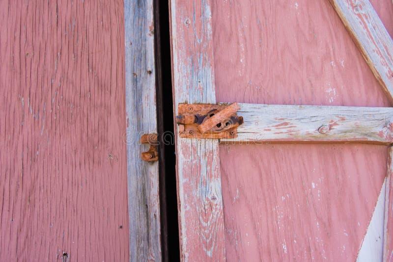 Vecchio ha sbiadito la porta di granaio rossa che è dipinta fotografie stock
