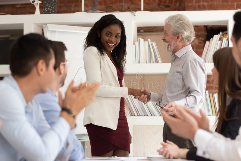 Vecchio handshake tollerante del responsabile che ricompensa l'impiegato di concetto africano felice della donna fotografia stock