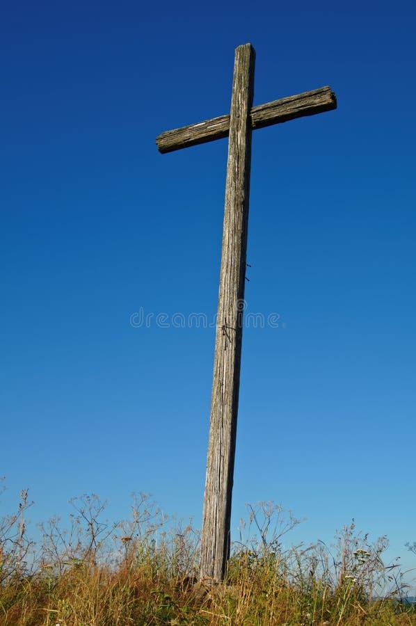 Vecchio incrocio di legno contro un fondo del cielo blu fotografia stock libera da diritti